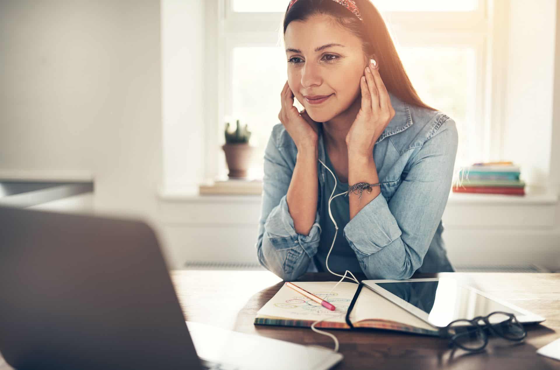 Woman with headphones transcribing