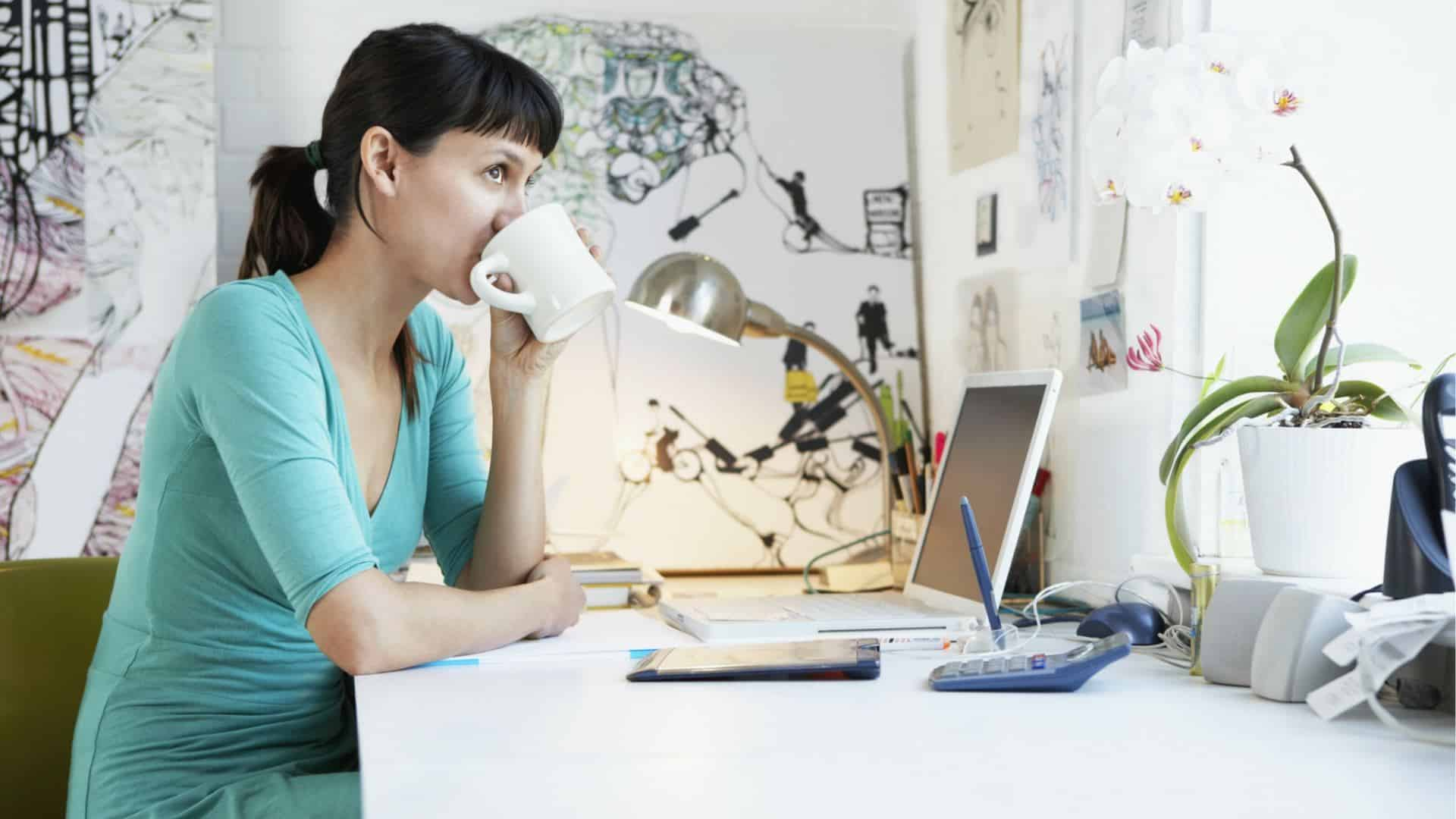 Woman drinking coffee working at home