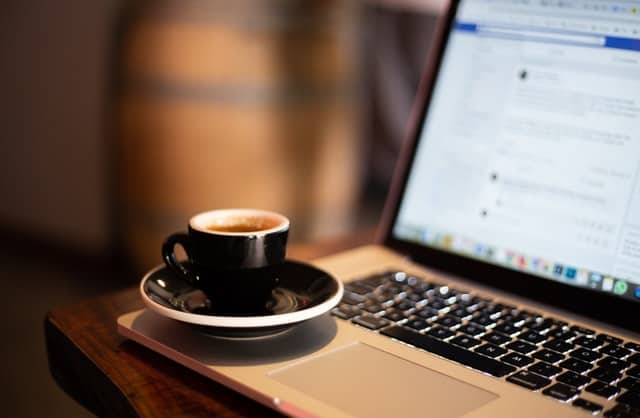 A cup of cappuccino on a saucer sitting on the corner or an open laptop displaying a social media page.