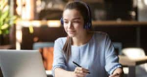 Focused woman wearing headphones using laptop